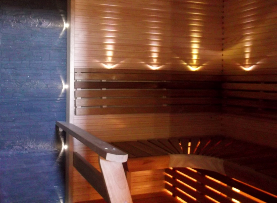 Tunnelmallinen sauna. Kiukaan takana kiviseinä. Selkänojassa ja kiukaan sivuilla ledi valot. Rakennusliike Harju-Heikkilä Oy.