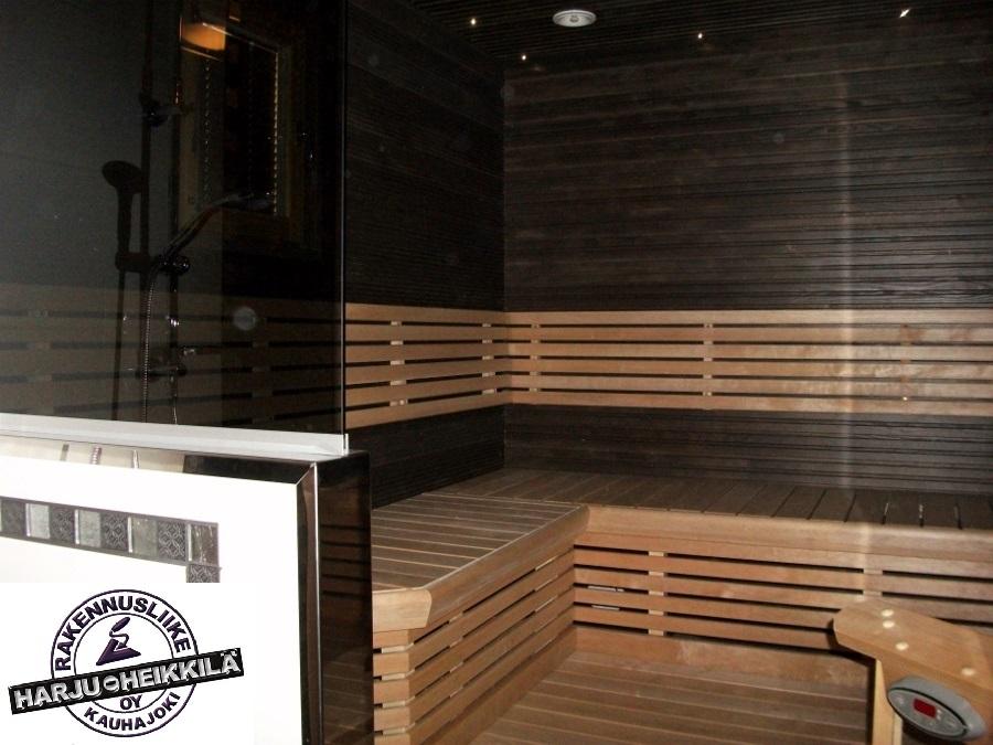 Sauna, jossa tummat seinät ja vaaleat lauteet. Rakennusliike Harju-Heikkilä Oy.